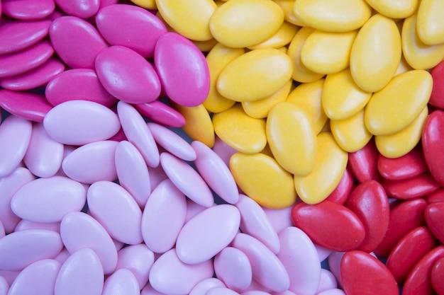 Un sacco di confetti di caramelle, cioccolato colorato su uno sfondo