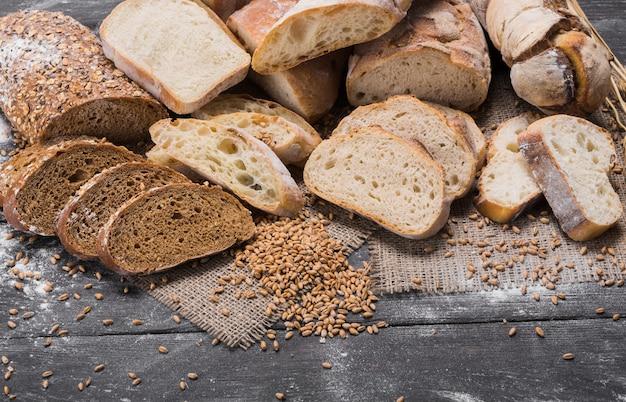 Pane a fette in abbondanza. concetto di panetteria e drogheria. fresco e sano grano intero affettato tipi di pagnotte bianche e segale, farina cosparsa sul tavolo in legno rustico, primo piano dell'alimento.