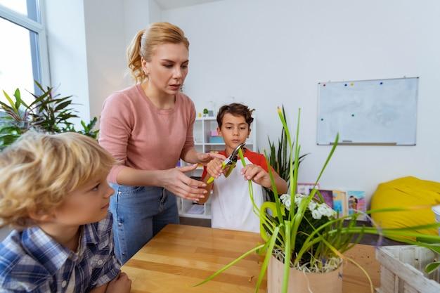 Pinze per tagliare. insegnante che aiuta un ragazzo dai capelli scuri a prendere le pinze per tagliare i bordi secchi della pianta verde