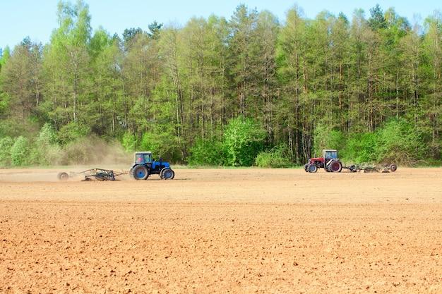 Trattore di aratura durante la coltivazione agricoltura lavora al campo con aratro