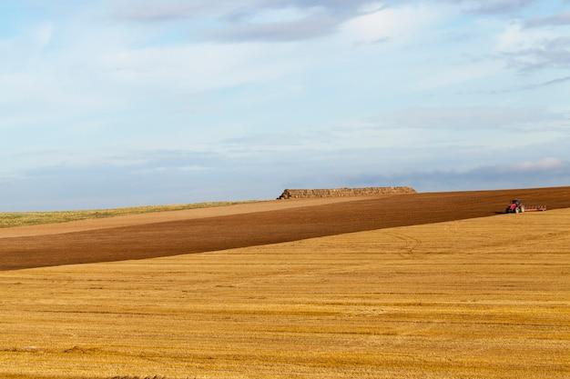 Arare i campi arabili dopo la raccolta del grano o di altri cereali con il trattore, sullo sfondo ci sono pile di paglia