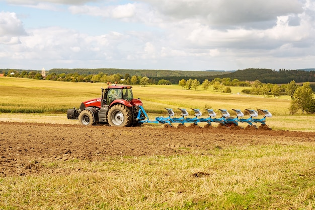 Arare la terra. agricoltore in trattore rosso che prepara la terra con l'aratro per la semina