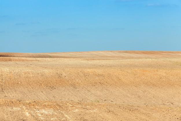 Campo agricolo arato, paesaggio con cielo blu durante la lavorazione del terreno