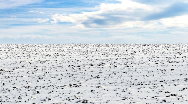 Campo di aratura. terreno coltivabile innevato, vista invernale