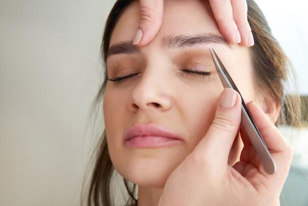 Spiumatura sopracciglia femminili con pinzette durante la correzione delle sopracciglia nel salone di bellezza