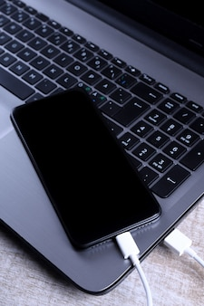Collegare il cavo usb, il caricabatterie, il caricamento, il caricamento e il trasferimento dei dati del telefono cellulare, smartphone con un laptop sul pavimento di legno, tavolo vista dall'alto