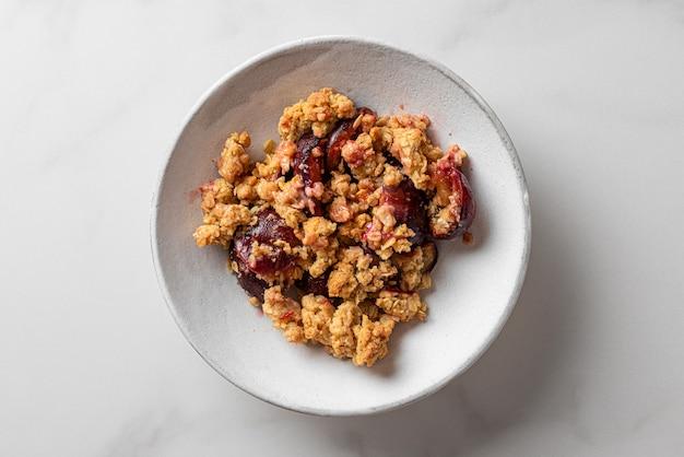 Dessert di crumble di prugne in un piatto su sfondo bianco per una gustosa colazione. vista dall'alto