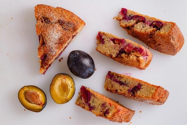 Pasta di prugne tagliata a pezzi, deliziosa torta di prugne su una lavagna bianca con decorazione di prugne fresche.