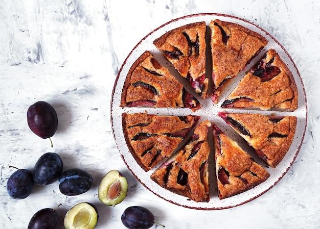 La torta di prugne viene tagliata a pezzi e adagiata su un piatto prugne fresche