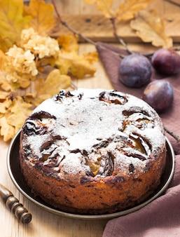 Torta di prugne con noci e cioccolato su uno sfondo di legno. stile rustico, messa a fuoco selettiva.