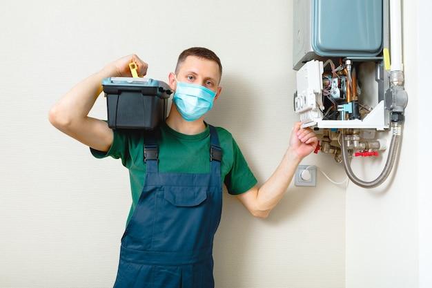 Idraulico si attacca cercando di risolvere il problema con l'impianto di riscaldamento residenziale. riparazione di una caldaia a gas
