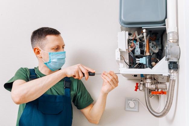 Idraulico attacca cercando di risolvere il problema con l'impianto di riscaldamento residenziale. riparazione di una caldaia a gas