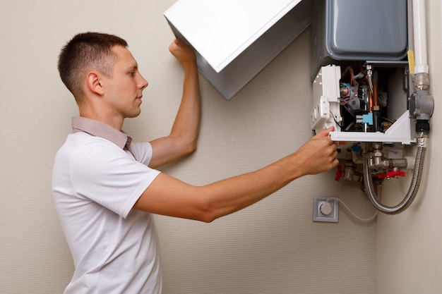 L'idraulico si attacca cercando di risolvere il problema con l'impianto di riscaldamento residenziale. riparazione di una caldaia a gas