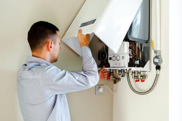 Idraulico si attacca cercando di risolvere il problema con l'attrezzatura di riscaldamento residenziale