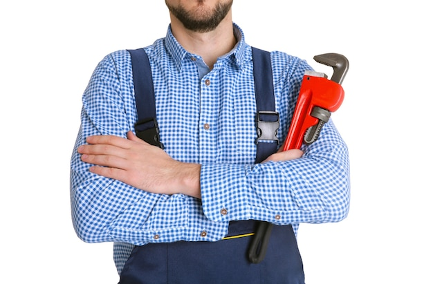 Idraulico in uniforme blu che tiene la chiave a tubo isolata su bianco
