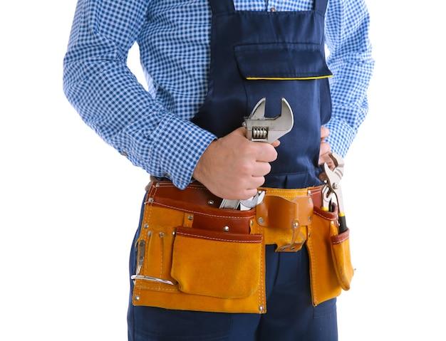 Idraulico in uniforme blu che tiene la chiave a vite isolata su bianco