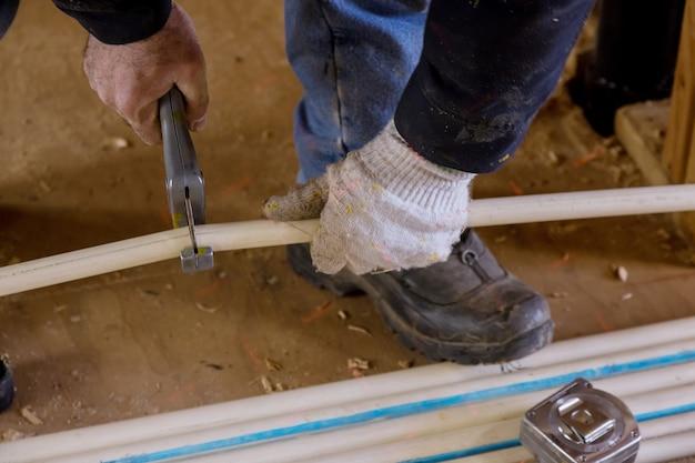 Idraulico che taglia il tubo delle linee d'acqua in pvc sulla nuova casa in costruzione