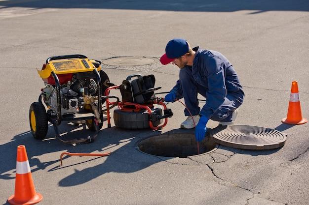 L'idraulico diagnostica un pozzo di scarico sulla strada utilizzando attrezzature speciali.