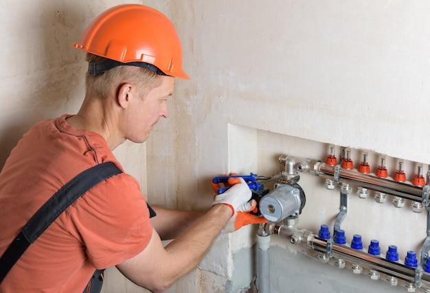 Idraulico che fissa una pompa dell'acqua in un sistema di riscaldamento a pavimento