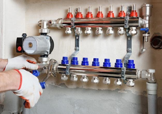 Un idraulico che fissa una pompa dell'acqua in un sistema di riscaldamento a pavimento