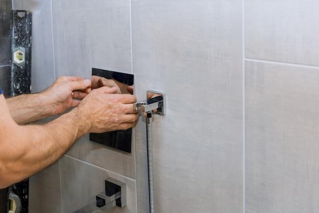 Mani dell'idraulico che fissano il miscelatore della doccia sul rubinetto moderno nel controllo del calore del bagno