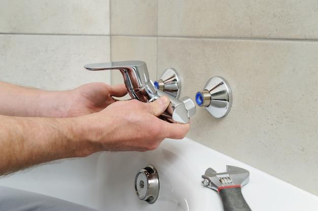 Idraulico che tiene un rubinetto del bagno e lo installa