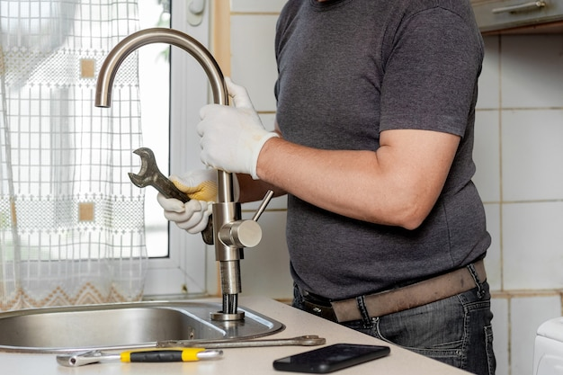 Un idraulico in cucina installa un nuovo rubinetto dell'acqua. riparazione del rubinetto in cucina vicino al lavello