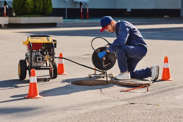 L'idraulico si prepara a risolvere il problema nella fogna. lavori di riparazione sulla risoluzione dei problemi.