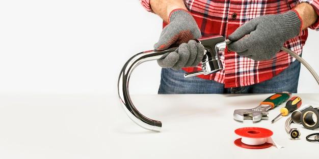 Idraulico avvitando un raccordo idraulico nel rubinetto contro uno sfondo grigio con copia spazio.