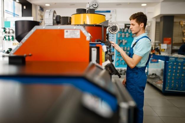Idraulico in uniforme scegliendo caldaia con forno in vetrina nel negozio idraulico. uomo con notebook che acquista ingegneria sanitaria in negozio, scelta scaldabagno