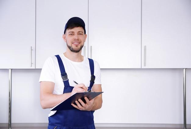 Idraulico in uniforme che tiene appunti in cucina
