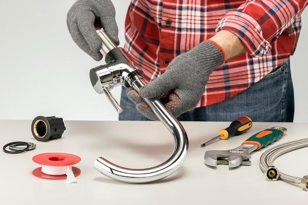 Idraulico al lavoro in una cucina o in un bagno, servizio di riparazione, assemblaggio e installazione del concetto.