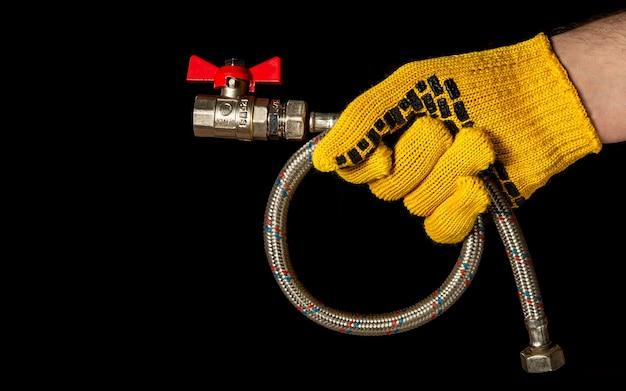 La mano guantata dell'impianto idraulico tiene il tubo flessibile dell'acqua ad alta pressione con le valvole a sfera