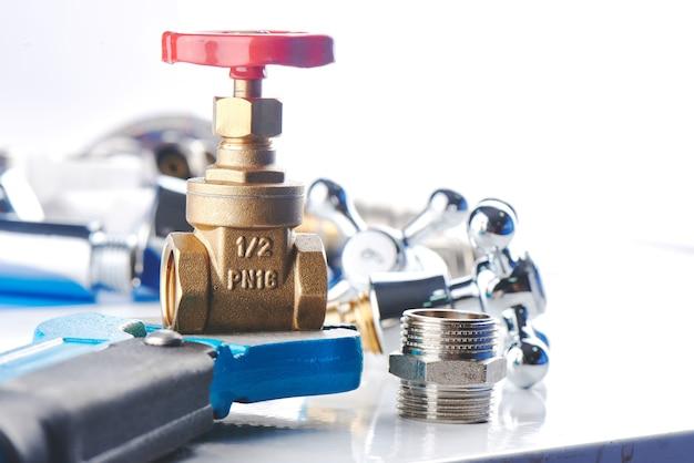 Parti e strumenti dell'impianto idraulico su una priorità bassa bianca