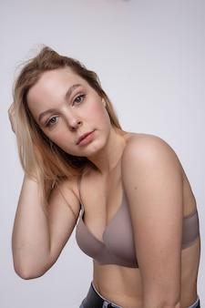 Donna caucasica grassottella che posa in biancheria beige, reggiseno su bianco