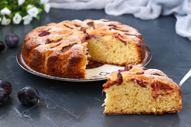 La torta di prugne si trova su un piatto su uno sfondo scuro, un pezzo di torta in primo piano, le prugne fresche sono sul tavolo