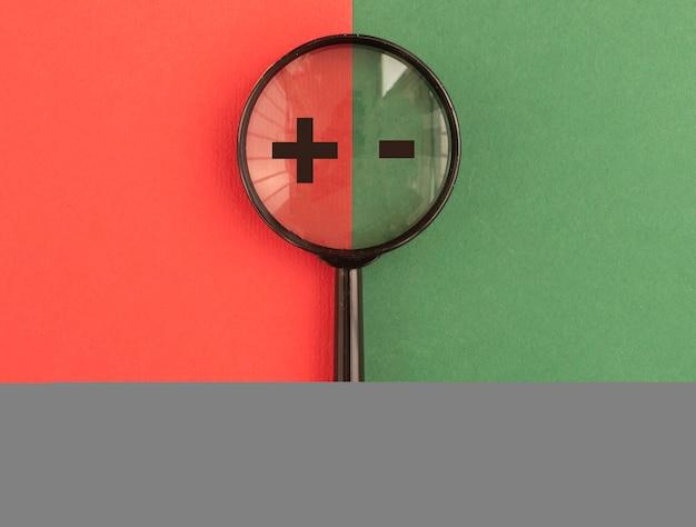 Segni più e meno attraverso la lente di ingrandimento su sfondo rosso e verde. concetto di confronto positivo e negativo, buono e cattivo.