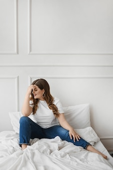 Ragazza di modello per taglie forti in jeans e maglietta bianca vuota che si siede sul letto. moda xxl. bellezza unica