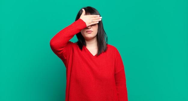 Donna graziosa di taglia più grande che copre gli occhi con una mano sentendosi spaventata o ansiosa, chiedendosi o aspettando ciecamente una sorpresa