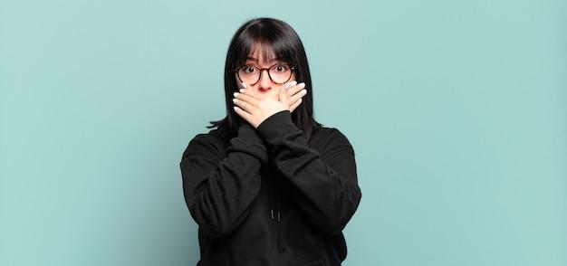Plus size bella donna che copre la bocca con le mani con un'espressione scioccata e sorpresa, mantenendo un segreto o dicendo oops