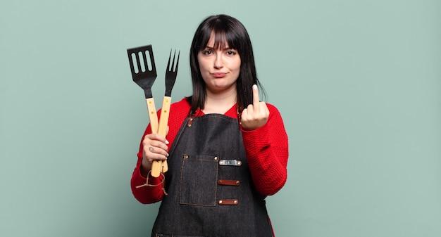 Plus size bella donna che si sente arrabbiata, infastidita, ribelle e aggressiva, lanciando il dito medio, contrattaccando