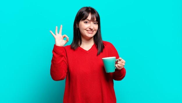 Plus size bella donna sentirsi felice, rilassata e soddisfatta, mostrando approvazione con un gesto ok, sorridente,