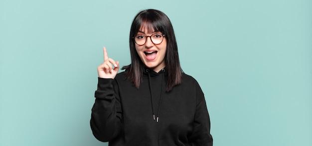 Plus size bella donna che si sente come un genio felice ed eccitato dopo aver realizzato un'idea, alzando allegramente il dito, eureka!