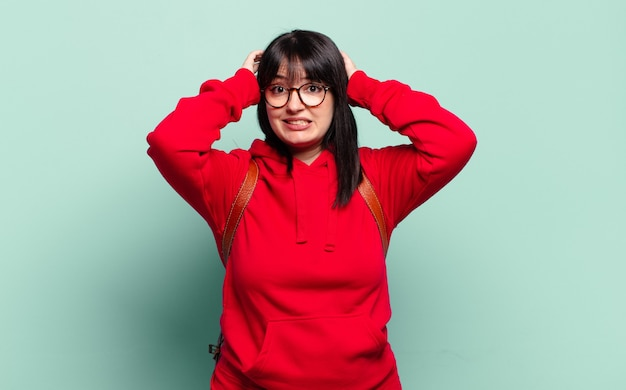 Donna graziosa di taglia grande che si sente stressata, preoccupata, ansiosa o spaventata, con le mani sulla testa, in preda al panico per errore