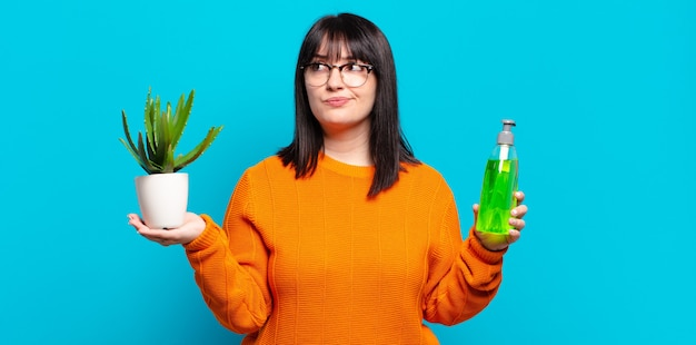 Plus size donna graziosa che tiene cactus. concetto di aloe vera