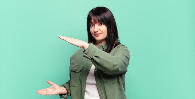 Donna graziosa di taglia più grande che tiene un oggetto con entrambe le mani sullo spazio della copia laterale, mostrando, offrendo o pubblicizzando un oggetto