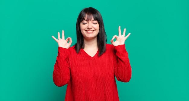 Taglie forti, bella donna che sembra concentrata e medita, si sente soddisfatta e rilassata, pensa o fa una scelta