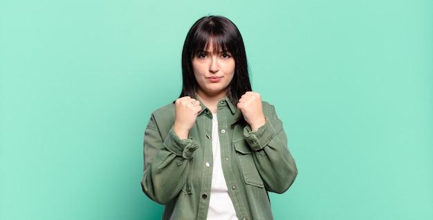 Plus size bella donna che sembra sicura di sé, arrabbiata, forte e aggressiva, con i pugni pronti a combattere in posizione di boxe