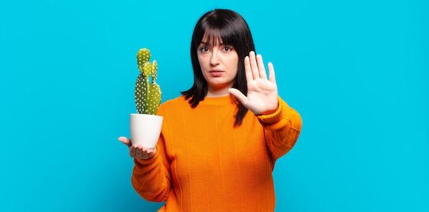 Plus size bella donna che sembra seria, severa, dispiaciuta e arrabbiata che mostra il palmo aperto che fa il gesto di arresto