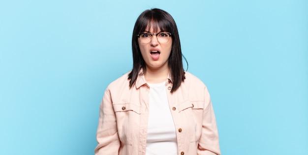 Plus size bella donna che sembra scioccata, arrabbiata, infastidita o delusa, a bocca aperta e furiosa